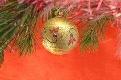 Jouet d'arbre : modèle d'or, jaune, de boule, pendant Noël et la nouvelle année sur une branche de pin sur un fond d'écarlate Images stock