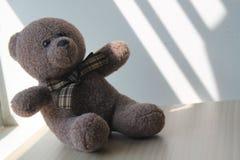 Jouet d'ours de Brown se reposant par la fenêtre dans les ombres Images libres de droits