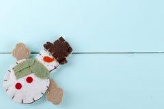 Jouet de bonhomme de neige sur un fond en bois Photographie stock libre de droits