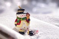 Jouet de bonhomme de neige sur la vraie neige Composition en Noël pour la carte de voeux photos libres de droits
