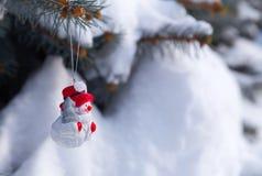 Jouet de bonhomme de neige sur un sapin images stock