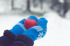 Jouet de coeur dans des mitaines de laine Concept de carte de jour de valentines Coeur rouge dans des mains Photos stock