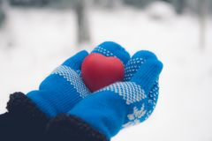 Jouet de coeur dans des mitaines de laine Concept de carte de jour de valentines Coeur rouge dans des mains Image stock