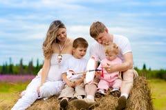 Jouet de lancement de famille heureuse se reposant sur la meule de foin Image stock