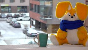 Jouet de lapin de peluche avec la tasse de thé se reposant sur le radiateur par la fenêtre en hiver blizzard banque de vidéos