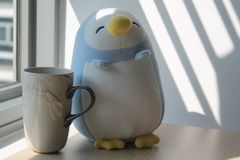 Jouet de pingouin avec la tasse se reposant par la fenêtre dans les ombres Photo libre de droits