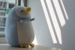Jouet de pingouin se reposant par la fenêtre dans les ombres Photos libres de droits