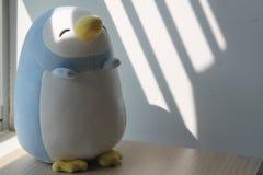 Jouet de pingouin se reposant par la fenêtre dans les ombres Image stock