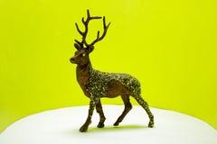 Jouet de Raindeer sur le fond vert au néon vibrant photos stock