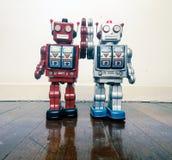 Jouet de robot de deux vintages heureux ensemble sur un plancher en bois Images libres de droits