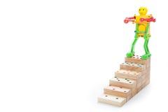 Jouet de robot se tenant sur des étapes supérieures de domino en bois, sur le dos de blanc Photo stock