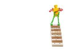 Jouet de robot se tenant sur des étapes supérieures de domino en bois, sur le dos de blanc Images libres de droits
