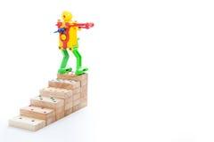 Jouet de robot se tenant sur des étapes supérieures de domino en bois, sur le dos de blanc Photographie stock libre de droits