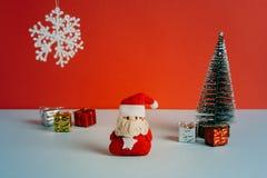 Jouet de Santa de feutre, cadeaux et arbre de Noël avec un flocon de neige dans le ciel sur le fond rouge Image libre de droits