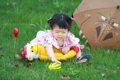 Jouet et boule innocents mignons de peluche de jeu de bébé sur la pelouse Image libre de droits