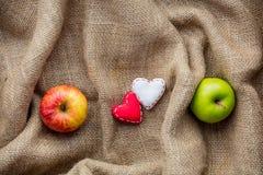 Jouet et pommes de forme de coeur sur le fond de jute Photos stock