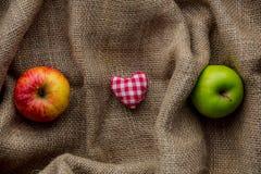Jouet et pommes de forme de coeur sur le fond de jute Photo stock