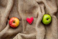 Jouet et pommes de forme de coeur sur le fond de jute Image stock