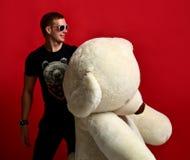 Jouet mou d'ours de nounours de prise d'homme grand comme présent à son amie pour la fête d'anniversaire Photos libres de droits