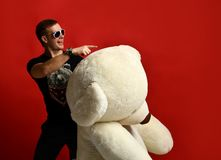 Jouet mou d'ours de nounours de prise d'homme grand comme présent à son amie pour la fête d'anniversaire Photographie stock libre de droits