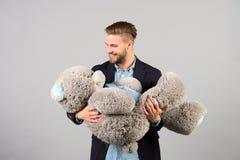 Jouet mou d'ours de nounours de prise d'homme grand en tant que présent Photo stock