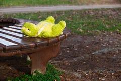 Jouet mou oublié isolé de grenouille se trouvant sur le banc dans le propriétaire de attente de parc Image stock