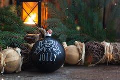 Jouet noir fait main de boule de vintage de Noël avec un espace rustique de copie de style de fond brûlant de lanterne photographie stock libre de droits