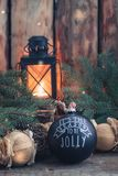 Jouet noir fait main de boule de vintage de Noël avec un espace rustique de copie de style de fond brûlant de lanterne photographie stock