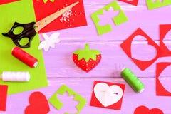 Jouet, outils et matériaux de couture Jouet de fraise de feutre, ciseaux, feuilles de feutre de rouge et de vert et chutes, fil,  Photos libres de droits