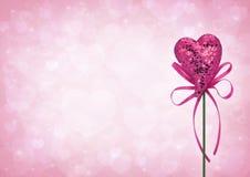 Jouet rose de coeur d'amour avec l'arc sur le fond rose-clair de tache floue Photographie stock
