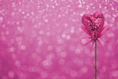 Jouet rose de coeur d'amour avec l'arc sur le fond rose de tache floue de bokeh, amour Images stock