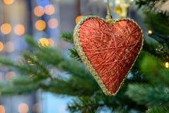 Jouet rouge de coeur accrochant sur l'arbre de Noël Photographie stock