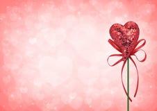 Jouet rouge de coeur d'amour avec l'arc sur le fond rouge de tache floue de coeur Photographie stock libre de droits