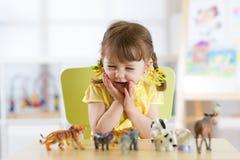 Jouets animaux heureux de jeux de petit enfant à la maison ou service de garderie photos libres de droits