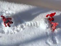Jouets construisant un bonhomme de neige au milieu de la neige blanche Images stock