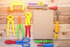 Jouets d'outils de travail et note de papier blanc sur un plancher en bois Photographie stock libre de droits