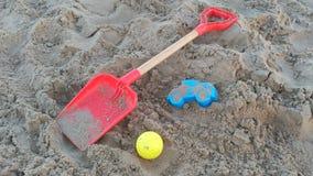Jouets dans le sable images stock