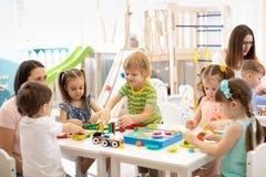 Jouets de jeu d'enfants de jardin d'enfants avec le professeur dans la salle de jeux à l'école maternelle réserve vieux d'isoleme photos libres de droits