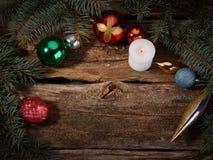 Jouets de Noël avec des branches d'arbre brûlant la bougie Images stock