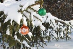 Jouets de Noël sur les branches couvertes de neige d'un sapin Photo stock