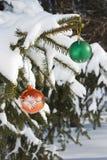Jouets de Noël sur les branches couvertes de neige d'un sapin Photographie stock