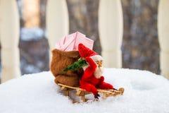 Jouets de Noël de vintage Gnome dans le chapeau rouge sur le traîneau en bois parmi le Sn Image libre de droits