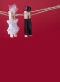 Jouets de pince à linge de jeunes mariés sur la corde à linge Femme abstraite dans la robe et l'homme de mariage blancs avec le c Photographie stock