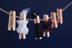 Jouets de pince à linge de jeunes mariés, corde à linge Femme abstraite dans le caractère blanc de robe et d'homme avec le chapea Photos libres de droits