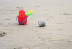 Jouets en plastique colorés sur la plage près de la mer Image libre de droits