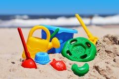 Jouets en plastique d'enfants sur la plage de sable Photographie stock