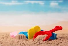 Jouets et château en plastique lumineux en sable contre la mer photos libres de droits