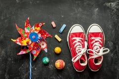 Jouets et espadrilles rouges sur le tableau noir - enfance Photos libres de droits