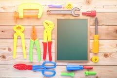 Jouets et tableau d'outils de travail sur un plancher en bois Image stock