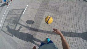 Joueur avec l'appareil-photo sur des passages de tête avec la boule parmi des sportifs banque de vidéos
